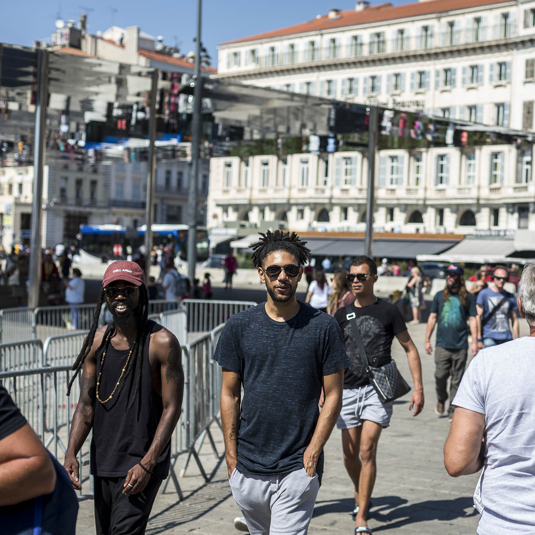 Two young Black men smiling at the camera stand out among the pedestrians walking through a public space on a summer day.