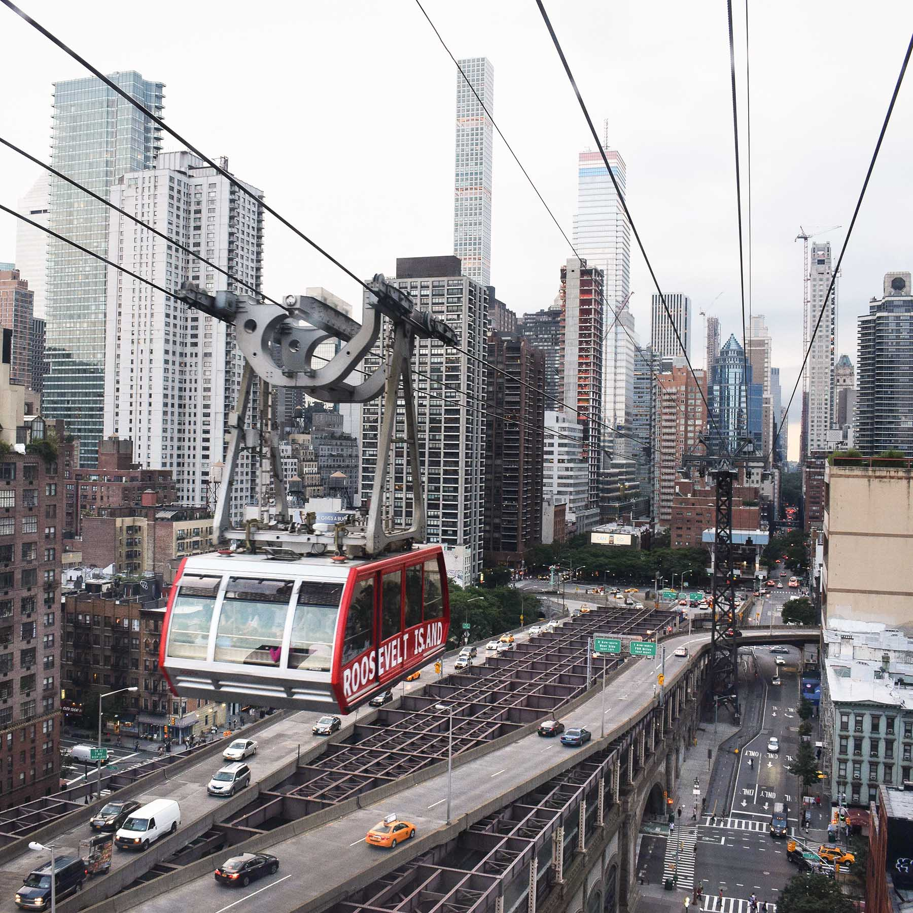 A cable car flies over an expressway, which is itself above city streets. In the background are skyscrapers.